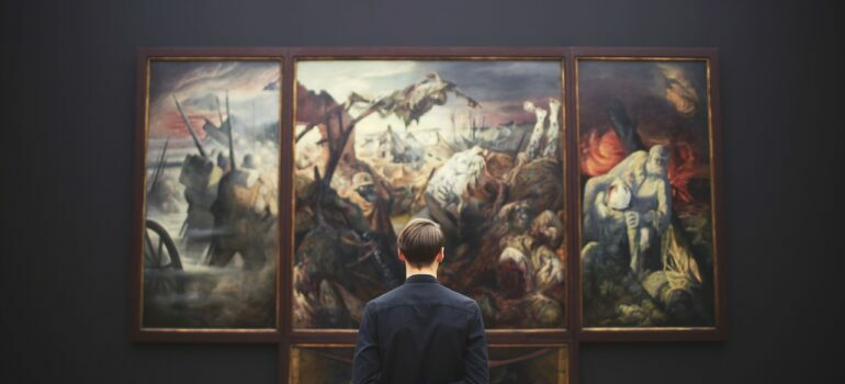 A man in black shirt admiring paintings.