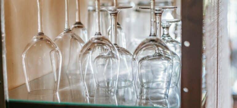 Clean glassware arranged upside down on a glass shelf.