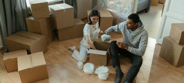 a couple unpacking a box after packing services Austin brought them into apartment